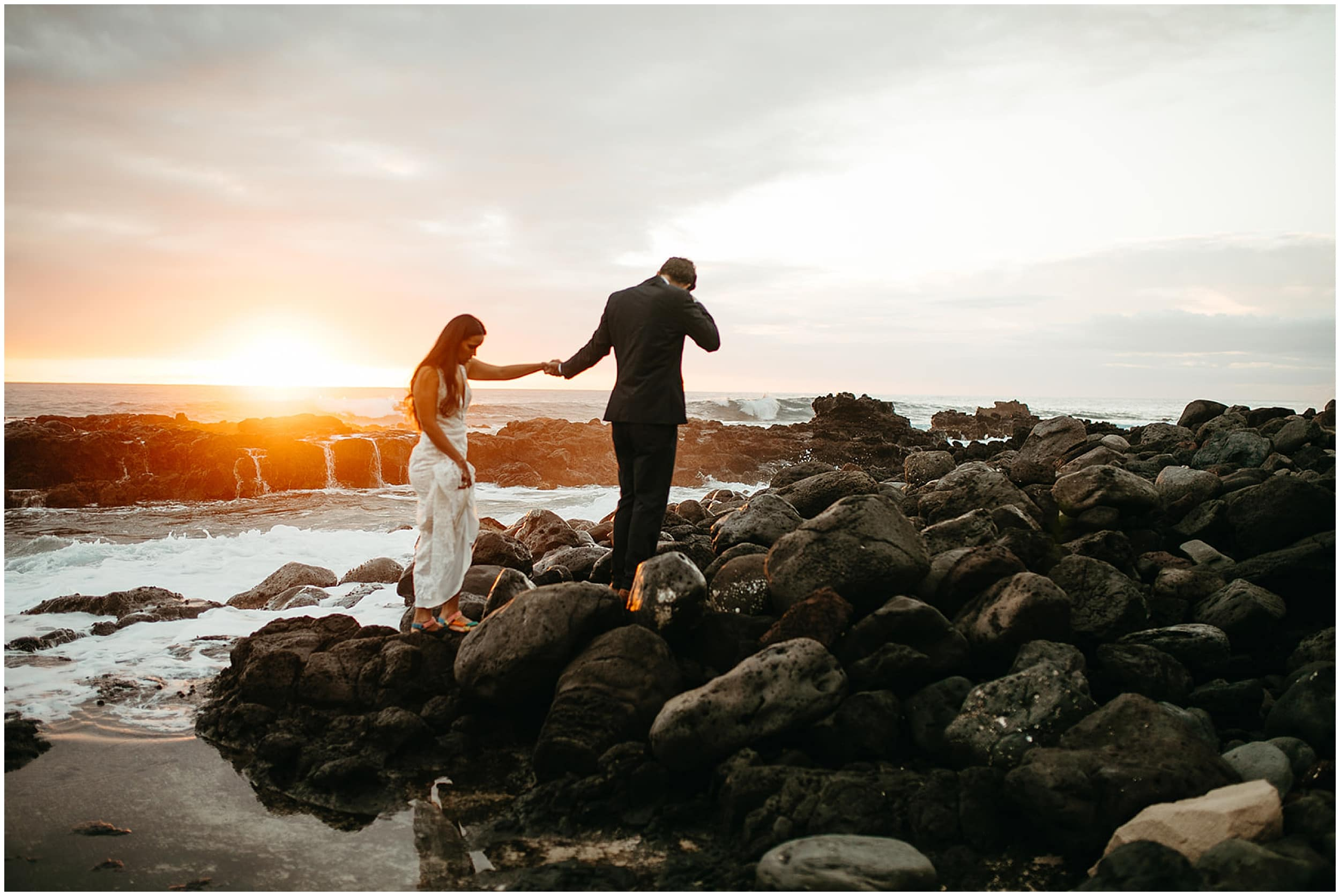 bride and groom walking on beach at sunrise