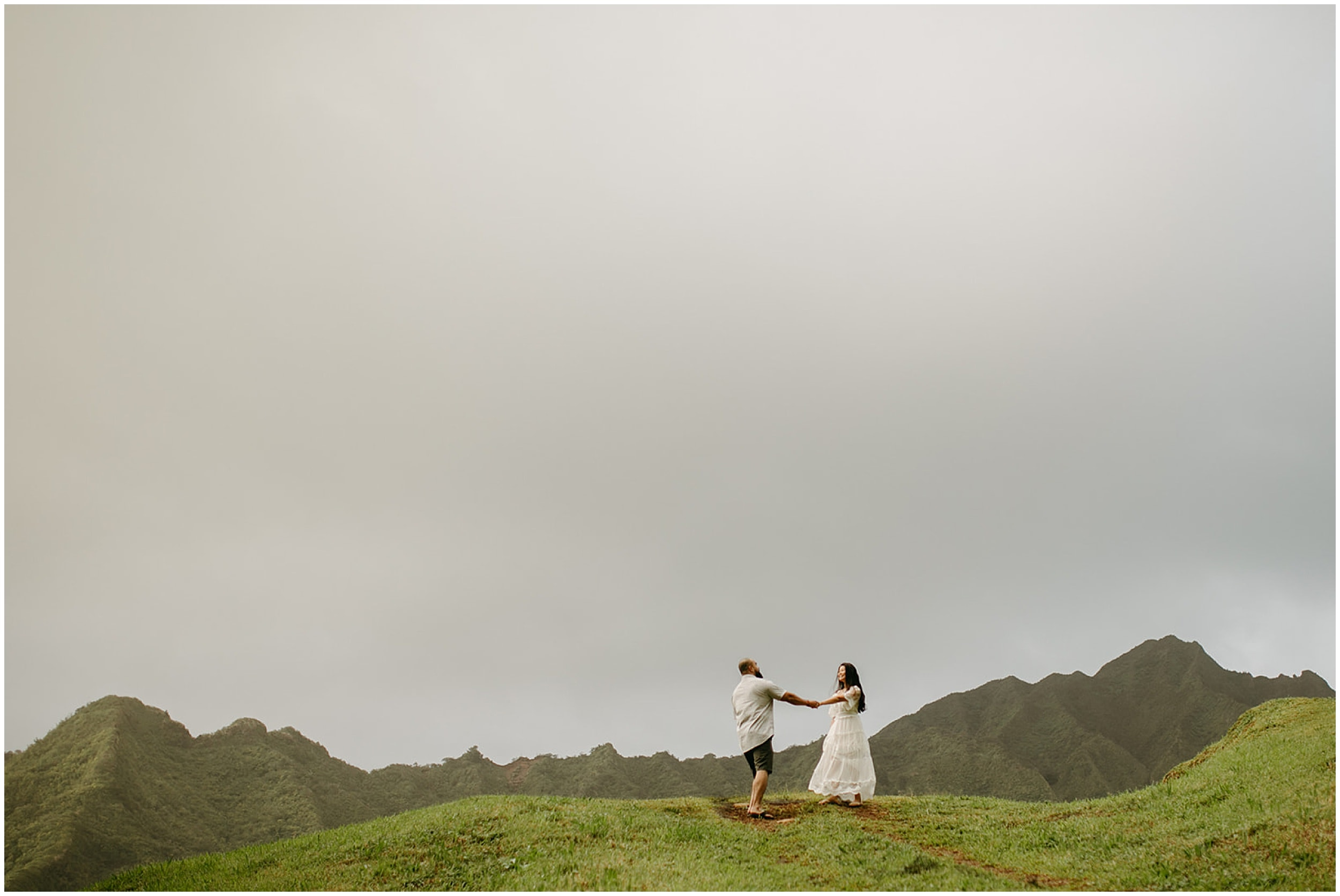 couple walking on grassy hill