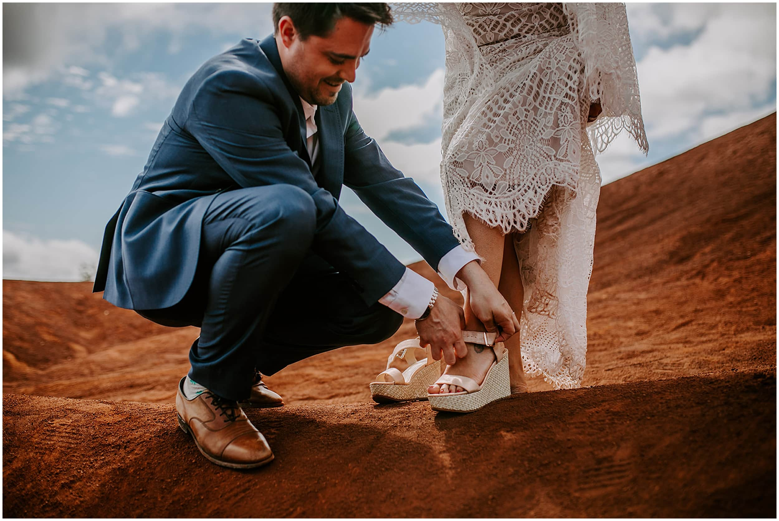 groom putting shoes on bride