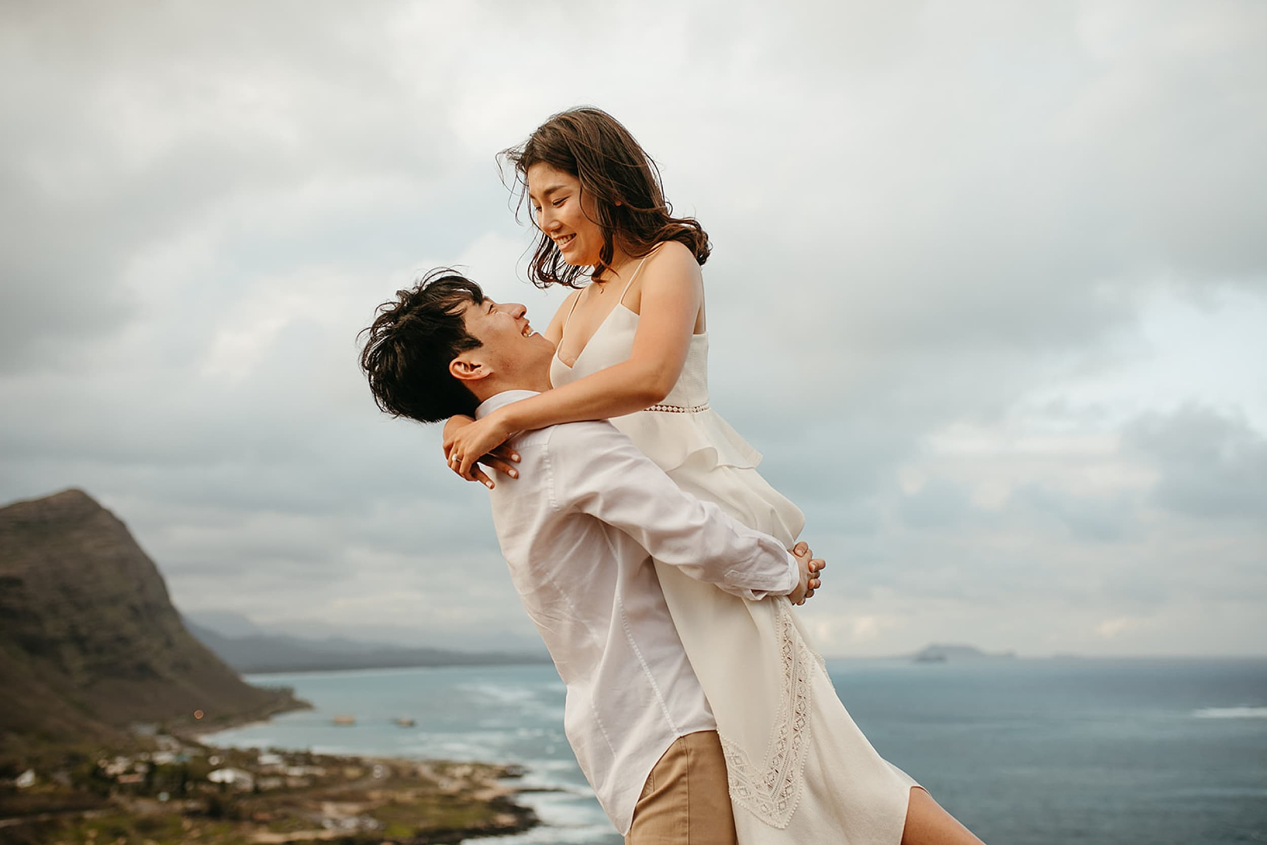 couple embracing on a cliff in Oahu