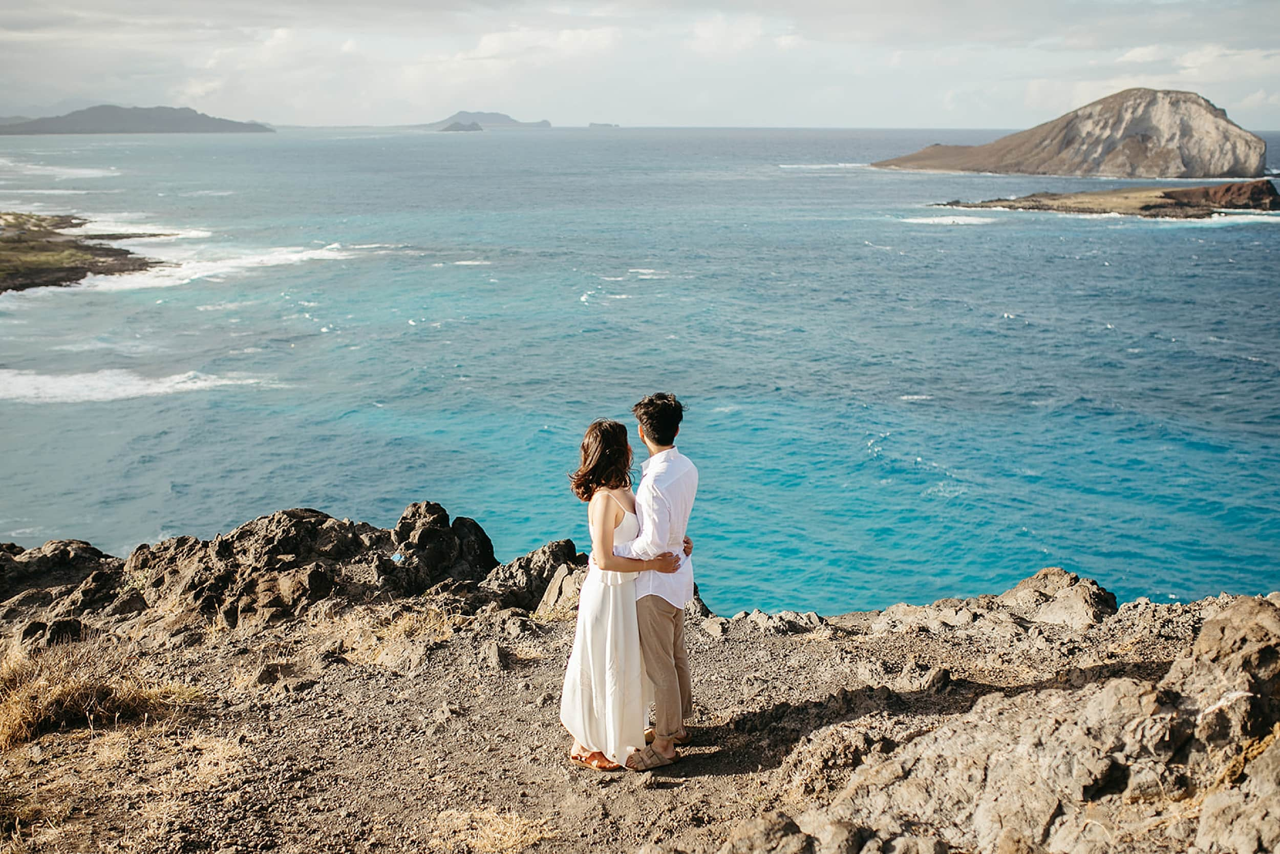 couple embracing on a cliff during an Oahu elopement